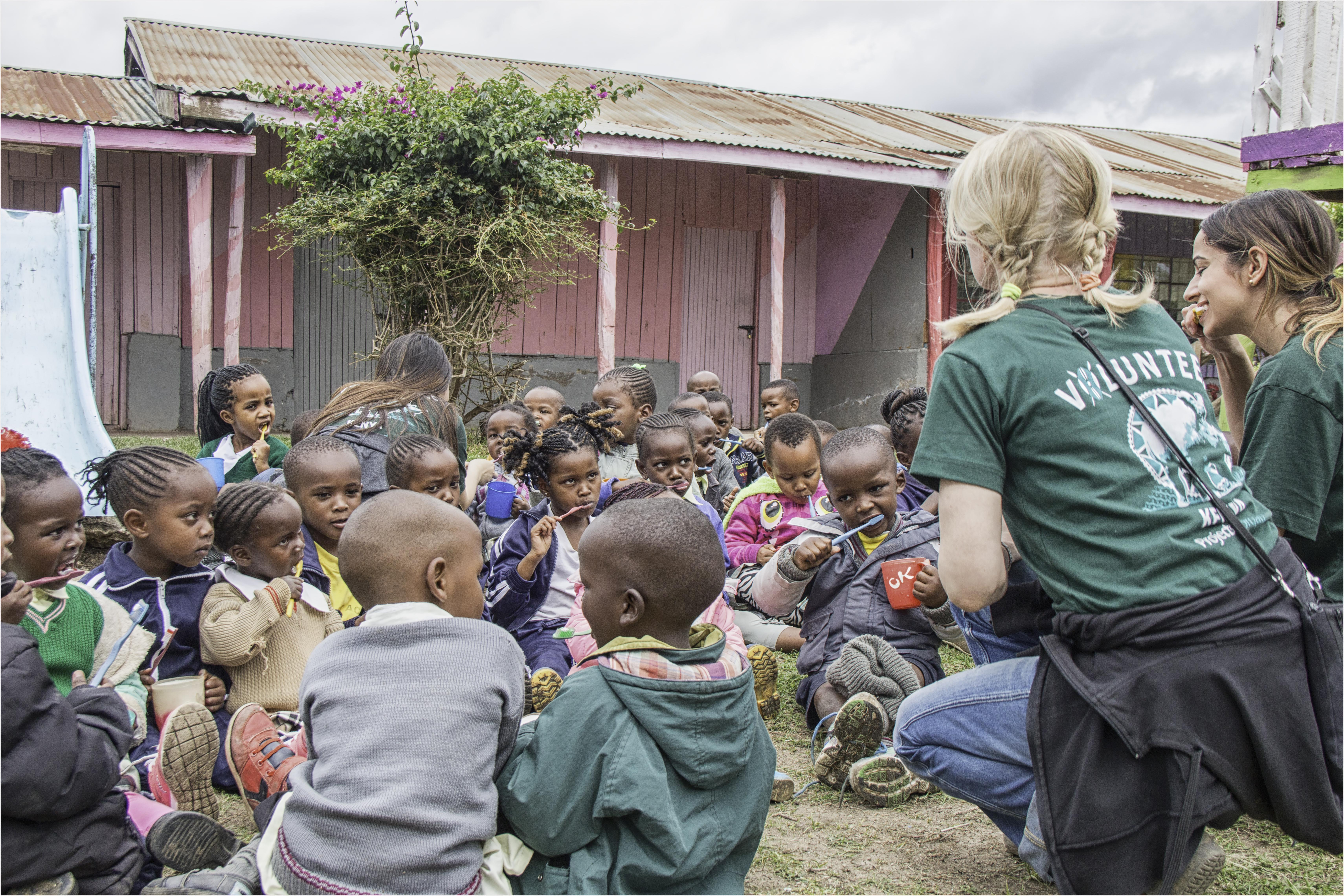 Volunteers talk with the children while they are eating as they complete volunteer work with children for teenagers in Kenya.
